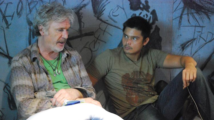 "In this handout photo taken March, 2010 and released by Portfolio Films Wednesday, April 3, 2013, Irish actor Patrick Bergin, left, talks with Filipino heartthrob Dingdong Dantes during a scene at the Cebu Provincial Detention and Rehabilitation Center in Cebu province, central Philippines. The Filipino inmates whose choreographed ""Thriller"" dance has attracted 52 million YouTube hits since 2007 are getting their own stories told in a movie ""Dance of the Steel Bars"". (AP Photo/Portfolio Films) NO SALES"