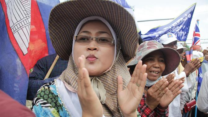A Cambodian woman cheers as opposition supporters wait outside the Chinese Embassy in Phnom Penh, Cambodia, Friday, Oct. 25, 2013. About 20,000 supporters on Friday wrapped up a three-day demonstration to petition foreign embassies and the U.N. for intervention in what they claim was a rigged election. (AP Photo)