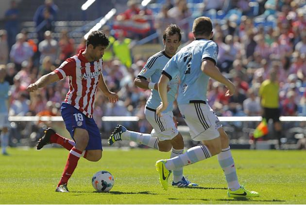 Atletico de Madrid's Diego Costa from Brazil, left, in action with Celta de Vigo's Andreu Fontas, right, Borja Oubina second left, as during a Spanish La Liga soccer match at the Vicente Calderon stad