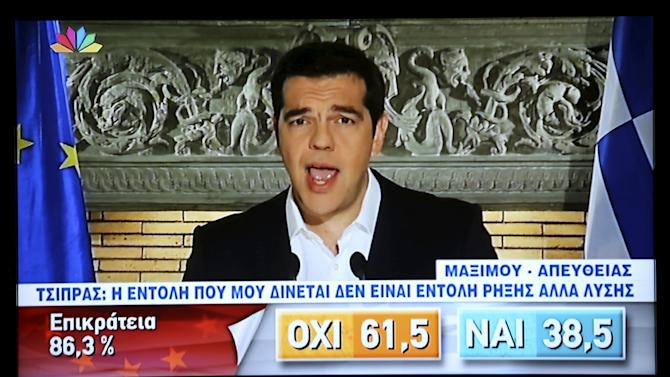 Greek Prime Minister Alexis Tsipras is seen on a television monitor as he addresses the nation in Athens
