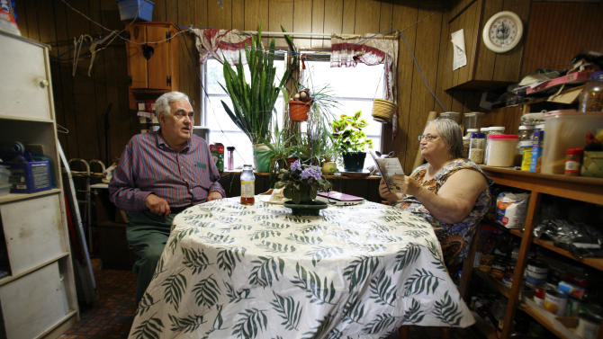 In this Sept. 15, 2011 photo, Bill Ricker talks with his ex-wife Judith Odyssey in the trailer home they share, in Hartford, Maine. They divorced around 1995 and she moved out. But he offered to let her move back in nine years ago when she was going through a rough time, and she now lives in the other end of the trailer. (AP Photo/Robert F. Bukaty)