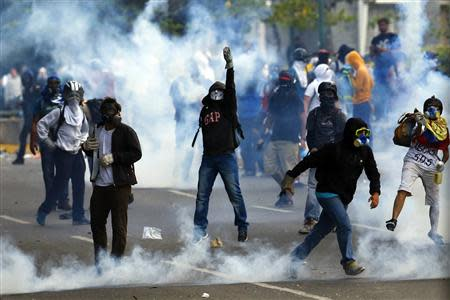 Anti-government protester throws stones to police during a protest at Altamira square in Caracas