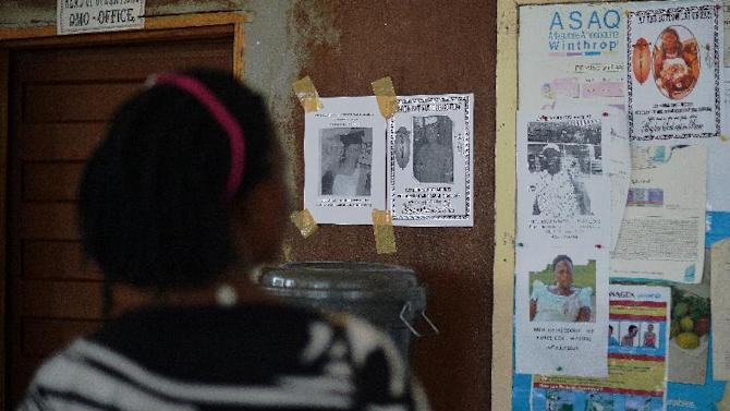 A woman looks at the obituary notices for medical staff who have died from the Ebola virus at the Kenema government hospital in Sierra Leone, August 16, 2014