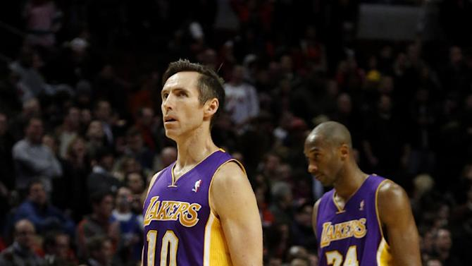 Los Angeles Lakers guards Steve Nash and Kobe Bryant walk off the court at the end of an NBA basketball game against the Chicago Bulls Monday, Jan. 21, 2013, in Chicago. The Bulls won 95-83. (AP Photo/Charles Rex Arbogast)