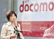 A pedestrian walks past a NTT docomo shop in Tokyo, 2009. Leading Japanese mobile phone carrier NTT DoCoMo said net profit in the fiscal first quarter to June inched higher on strong smartphone sales