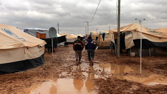 Two Syrian refugees walk among tents, surrounded by water and mud, at Zaatari Syrian refugee camp, near the Syrian border in Mafraq, Jordan, Tuesday, Jan. 8, 2013. Syrian refugees in a Jordanian camp attacked aid workers with sticks and stones on Tuesday, frustrated after cold, howling winds swept away their tents and torrential rains flooded muddy streets overnight. Police said seven aid workers were injured. (AP Photo/Mohammad Hannon)