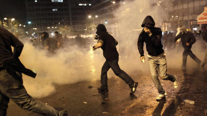 Backdropped by tear gas thrown by police, protesters run for cover during clashes with police, near the parliament in Athens, Wednesday Nov. 7, 2012. Greece's fragile coalition government faces its toughest test so far when lawmakers vote later Wednesday on new painful austerity measures demanded to keep the country afloat, on the second day of a nationwide general strike. AP Photo/Petros Giannakouris)