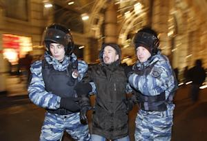 Police officers detain a protester during an unsanctioned…
