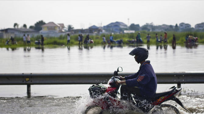 A motorcyclist rides through a flooded road from an overflowing canal as residents catch fish on the other side on the outskirts of Bangkok, Thailand Thursday, Oct. 20, 2011. Thailand's Prime Minister Yingluck Shinawatra acnowledged Thursday that efforyts to block floodwaters from entering the capital are failing and authorities will instead risk potential overflow with a controlled release of water through the city's canals. (AP Photo/Kantachat Raungratanaampon)