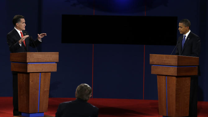 Republican presidential nominee Mitt Romney answers a question and President Barack Obama listens during the first presidential debate at the University of Denver, Wednesday, Oct. 3, 2012, in Denver. (AP Photo/Charlie Neibergall)
