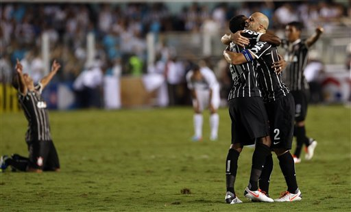 Corinthians' Alessandro (2) embraces teammate Gil as they celebrate at the end of the final match of the Sao Paulo state soccer league against Santos, in Santos, Brazil, Sunday, May 19, 2013. Corinthi