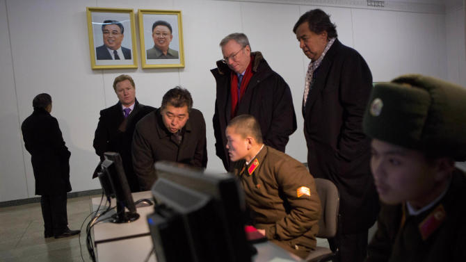 Executive Chairman of Google, Eric Schmidt, back row left, and former Governor of New Mexico Bill Richardson, back row right, look at North Korean soldiers working on computers at the Grand Peoples Study House in Pyongyang, North Korea on Wednesday, Jan. 9, 2013. (AP Photo/David Guttenfelder)