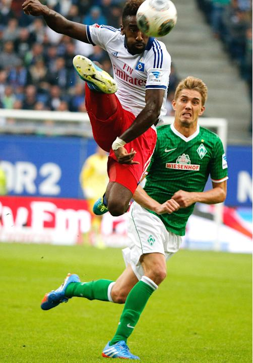 Bremen's Nils Petersen, right,  right, challenges  for the ball with Hamburg's Johan Djourou during the German Bundesliga soccer match between Hamburger SV and SV Werder Bremen  in Hamburg, Germany, S