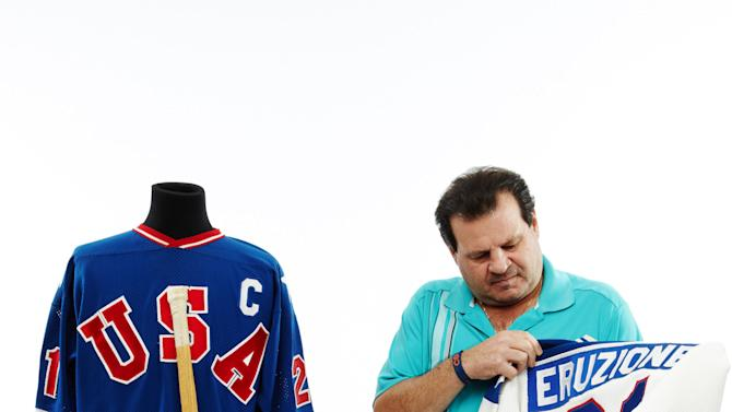 """This Dec. 12, 2012 handout photo, provided by Heritage Auctions, shows former United States Olympic hockey player Michael Eruzione in Dallas with jerseys and the hockey stick from his sensational winning goal against the Soviet Union hockey team at the 1980 Winter Olympics. The """"Miracle On Ice"""" paraphernalia will be offered by Dallas-based Heritage Auctions in New York on Feb. 22, on the 33rd anniversary of that historic game. (AP Photo/Courtesy of Heritage Auctions)"""