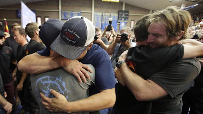 Firefighters embrace during a memorial service Monday, July 1, 2013, in Prescott, Ariz., honoring their 19 fellow firefighters killed battling a wildfire near Yarnell, Ariz., Sunday. The elite crew of firefighters was overtaken by the out-of-control blaze as they tried to protect themselves from the flames under fire-resistant shields. (AP Photo/Chris Carlson)