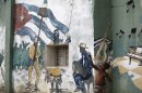 A boy plays with a catapult on a street beside a wall painted with a mural in Havana