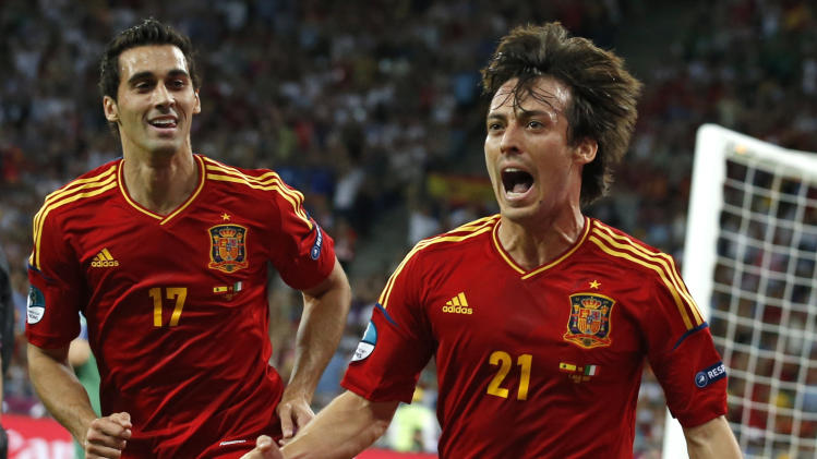 Spain's David Silva, right, celebrates flanked by his teammate Alvaro Arbeloa after scoring during the Euro 2012 soccer championship final  between Spain and Italy in Kiev, Ukraine, Sunday, July 1, 2012. (AP Photo/Jon Super)