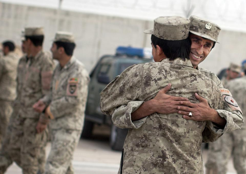 Afghan National policemen embrace each other after a morning drill at their base in Lashkar Gah, Helmand Province, Afghanistan, Thursday, Oct 18, 2012.  Afghanistan's police are routinely targeted by insurgent attacks in southern Afghanistan, one of the deadliest regions in the country. (AP Photo/Anja Niedringhaus)