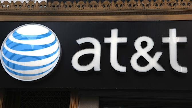 FILE-This May 6, 2012, file photo, shows an AT&T sign at a store in New York. Following in Verizon's footsteps, AT&T said Wednesday, July 18, 2012, it will introduce wireless plans that let subscribers connect up to ten devices. Connected phones get unlimited calling and texting, and all devices get wireless data access. The devices tap into a limited pool of data usage, which get renewed each month.  (AP Photo/CX Matiash, File)