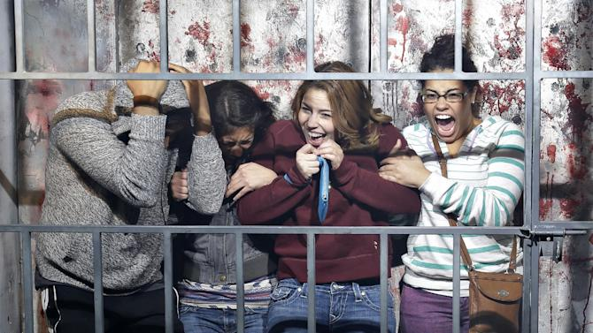 """In this Oct. 27, 2014, photo, people react to a mock execution in the Gates of Hell haunted house in Las Vegas. The haunted house is billed as an """"R-rated haunted attraction"""" and according to JT Mollner, a managing partner of Freakling Bros that runs the attraction, about one in five groups are so terrified they exit the house early. (AP Photo/John Locher)"""