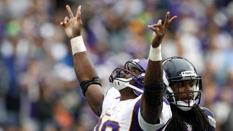 Minnesota Vikings' Adrian Peterson reacts to scoring his second touchdown of the game as Seattle Seahawks' Richard Sherman stands at right, in the first half of an NFL football game, Sunday, Nov. 4, 2012, in Seattle. (AP Photo/Elaine Thompson)