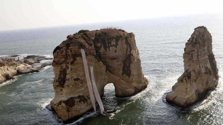 Activists roll down banners on Pigeon Rocks in Beirut