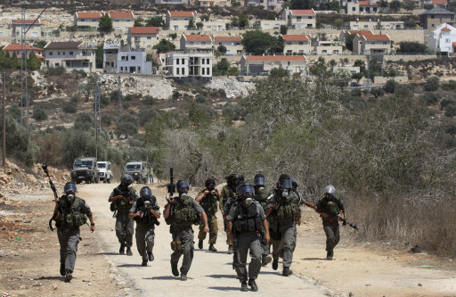 Israeli border police chase Palestinian protesters demonstrating demanding access to land in the area of Kufr Qaddum near the northern West Bank Jewish settlement of Kdumim, seen in the back, Friday, Aug. 19, 2011.(AP Photo/Nasser Ishtayeh)