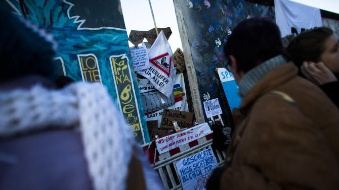 Protesters stand around a poster-covered hole in the East Side Gallery section of the former Berlin Wall in Berlin, Monday, March 4, 2013. After massive protest an investor suspended the removal of a section of the historic stretch of the Berlin Wall known as the East Side Gallery to provide access to a riverside plot where luxury condominiums are being built. The German posters reads from top: ' Culture Seller', ' Spree Riverside For All', 'Exchange City Palace...', 'All Wheels Stand Still If A Strong Arm Will It', and 'History Must Be Visible For Our Children'. (AP Photo/Markus Schreiber)