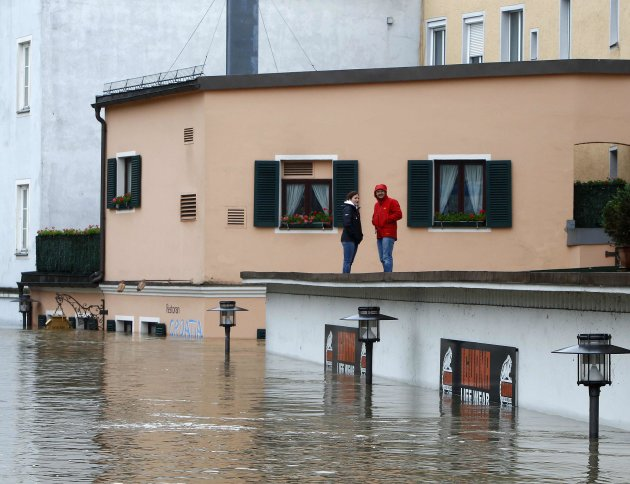 People stand on roof of building and look at flooded street in the centre of Passau