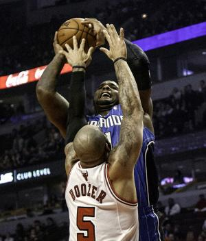 Chicago Bulls' Carlos Boozer (5) tries to block a shot by Orlando Magic's Glen Davis during an NBA basketball game in Chicago on Tuesday, Nov. 6, 2012. (AP Photo/Charles Cherney)