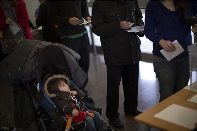A boy watches as voters holding ballot papers queue to cast their votes at a polling station in Barcelona, Spain, on Sunday, Nov. 25, 2012. Voters in Catalonia begin casting their ballots in regional