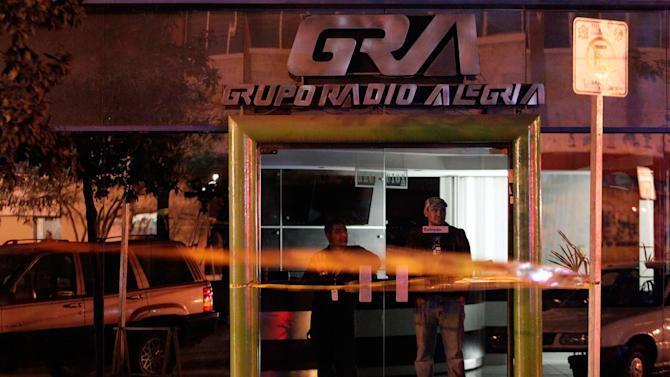 Workers look from inside a radio station at a crime scene where a man was killed in Monterrey