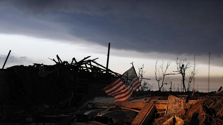 At sunrise Tuesday May 21, 2013, an American flag blows in the wind atop the rubble of a destroyed home in Moore, Okla., A huge tornado roared through the Oklahoma City suburb Monday, flattening entire neighborhoods and destroying an elementary school.   (AP Photo/Brennan Linsley)
