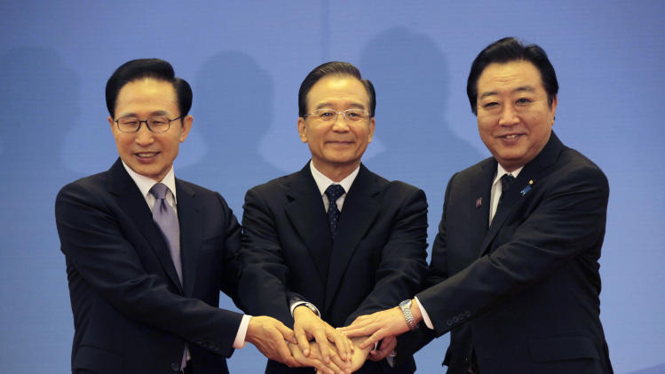 South Korea's President Lee Myung-bak, left, China's Premier Wen Jiabao, center, and Japan's Prime Minister Yoshihiko Noda hold their hands together as they pose for photographs ahead of the fifth trilateral summit among the three nations in Beijing, Sunday, May 13, 2012. (AP Photo/Petar Kujundzic, Pool)