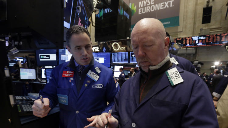 Specialist Jason Hardzewicz, left, and trader John Doyle work on the floor of the New York Stock Exchange Wednesday, Jan. 8, 2014.Stocks are mostly lower in early trading as investors hold back ahead of the release of the latest news from the Federal Reserve. (AP Photo/Richard Drew)