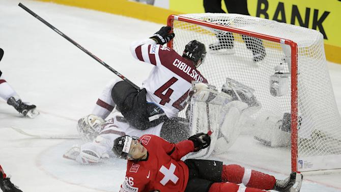 Switzerland's Reto Suri, front, slides on ice as Latvia's Oskars Cibulskis, back top, collides with Latvia's Edgars Masalskis, back bottom, during the Hockey World Championships Group A match in Prague, Czech Republic, Wednesday, May 6, 2015. (AP Photo/Petr David Josek)