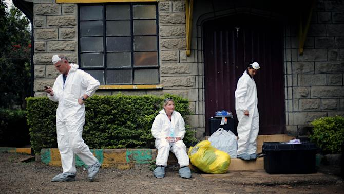 Foreign investigators take a break at the city morgue in Nairobi, Kenya, Thursday, Sept. 26, 2013. Forensic experts from around the world, including the U.S., Britain and Germany, continued their work Thursday, carrying out fingerprint, DNA and ballistic analysis, said police spokeswoman Gatiria Mboroki. More than 60 people were killed when militants entered the Westgate Mall on Saturday, firing assault rifles and throwing grenades. (AP Photo/Jerome Delay)