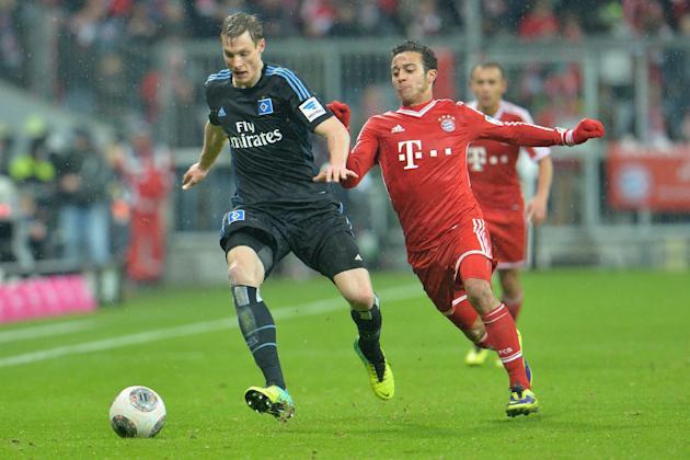 Bayern's Thiago Alcantara of Spain, right, and Hamburg's Marcell Jansen challenge for the ball   during  the German first division Bundesliga soccer match between FC Bayern Munich and Hamburge