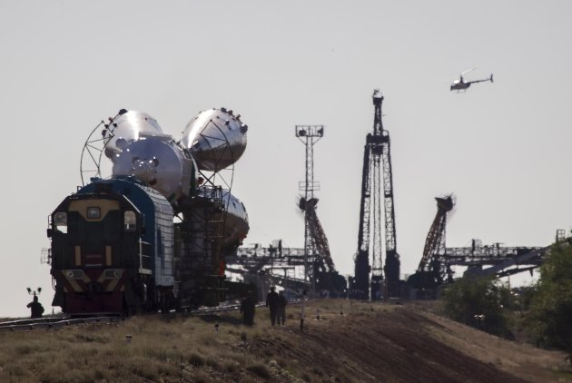 A police helicopter flies next to the Soyuz TMA-09M spacecraft as it is transported to its launch pad at Baikonur cosmodrome