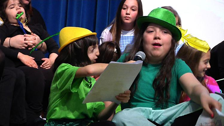 "In this Feb. 4, 2012 image made from video, 9-year-old Clara Beatty helps Zuzu Smith with her lines during a play in Winnetka, Ill. Clara is a ""buddy mentor"" for the Special Gifts Theatre, a drama troupe for children with special needs. Her mother, Janet, says at home or school or church, there, people know her. To them, she is just Clara - the funny, kind girl who wants to be a doctor when she grows up, who's quick to help classmates with homework when she finishes her own. (AP Photo/Martha Irvine)"