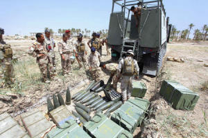 Iraqi soldiers load artillery shells onto a vehicle…