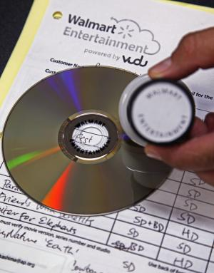 """A """"Walmart Entertainment"""" stamp in indelible ink has been placed on a disc, preventing any further conversion, but allowing it to still be played, at a Wal-Mart store in Rosemead, Calif., Wednesday, April 11, 2012. Wal-Mart is set to unveil its """"disc-to-digital"""" service for converting old DVDs into an online library that is available over the Internet. The fee it will charge per disc is meant to cover the cost of hosting and delivering reams of movie files to various devices. The world's largest retailer also aims to keep drawing customers to its big-box stores as their movie-watching habits change. (AP Photo/Reed Saxon)"""