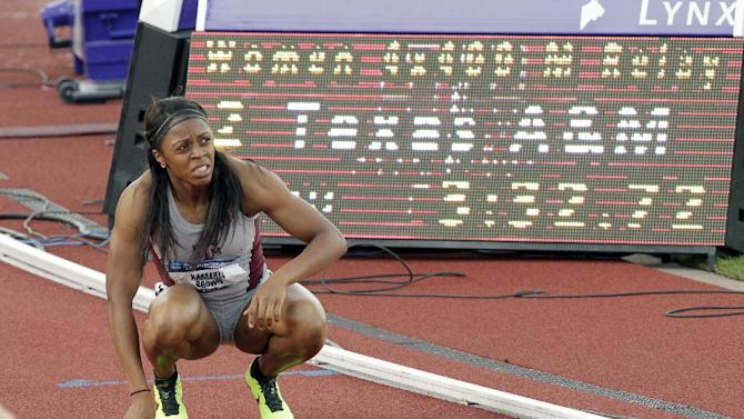 Texas A&M's Kamaria Brown rests on the track after finishing the anchor leg of the 4x100-meter preliminary race during the NCAA Track and Field Championships in Eugene, Ore., Thursday, June 6, 2013. Texas qualified for the finals. (AP Photo/Don Ryan)