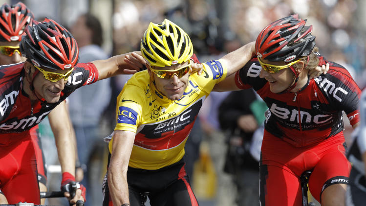 Tour de France winner Cadel Evans of Australia is hugged by his teammates as he crosses the finish line of the 21st stage of the Tour de France cycling race over 95 kilometers (59 miles) starting in Creteil and finishing in Paris, France, Sunday July 24, 2011. (AP Photo/Laurent Cipriani)