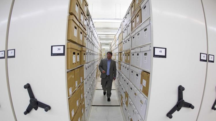 In this Wednesday, Oct. 17, 2012 photo, Georgia State Archivist Chris Davidson walks through shelves housing documents at the Georgia State Archives in Morrow, Ga. The Georgia State Archives will remain open to the public two days a week after an uproar over plans to limit access to appointments only for six days a month, state officials said Thursday, Oct. 18, 2012. Gov. Nathan Deal and Secretary of State Brian Kemp said $125,000 of a planned $733,000 cut in funding would be restored. (AP Photo/John Bazemore)