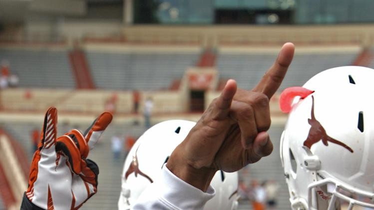 "Texas coach Charlie Strong gives the ""hook 'em horns"" sign while his players raise their helmets after the Orange and White spring NCAA college football game, Saturday, April 19, 2014, in Austin, Texas. (AP Photo/Michael Thomas)"