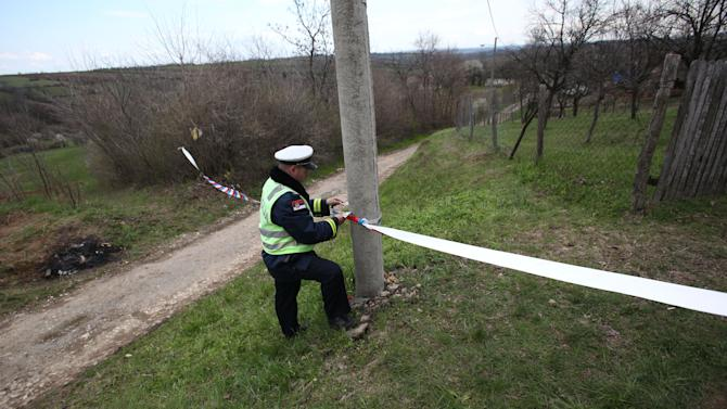 A police officer prepares police tape in the village of Velika Ivanca, Serbia, Tuesday, April 9, 2013. A 60-year-old man gunned down 13 people, including a baby, in a house-to-house rampage in the quiet village on Tuesday before trying to kill himself and his wife, police and hospital officials said. Belgrade emergency hospital spokeswoman Nada Macura said the man, identified as Ljubisa Bogdanovic, used a handgun in the shooting spree at five houses. The dead included six women. (AP Photo/Darko Vojinovic)