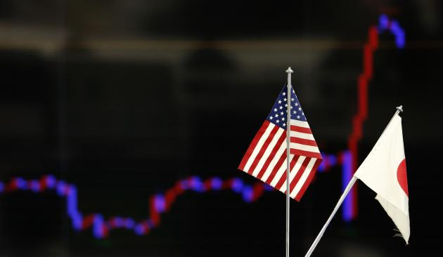 The national flags of Japan and the U.S. are seen in front of a monitor displaying a graph of recent fluctuations of the Japanese yen's exchange rate against the U.S. dollar at a foreign exchange