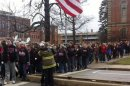 A Chardon firefighter embraces a high school student during a one year anniversary memorial march for three murdered classmates in Chardon