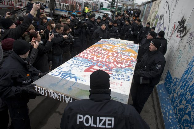 Police carry away a protester's styrofoam copy of a segment of the Berlin Wall at a demonstration against the removal of several segments of the East Side Gallery in Berlin